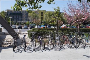 Yes, the Caltrain station provides bike racks -- and people are using them. But look carefully at this picture. Beyond the bikes the valuable land adjacent to the train station is consumed by surface parking lot.