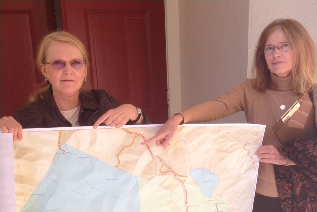 Elizabeth Terry Reynolds (left) and her sister Grace Terry show a map of family land in Roanoke County. The current iteration of the proposed Mountain Valley Pipeline route would cut through family land, and a construction access road would run through land held in a conservation easement (seen in blue).